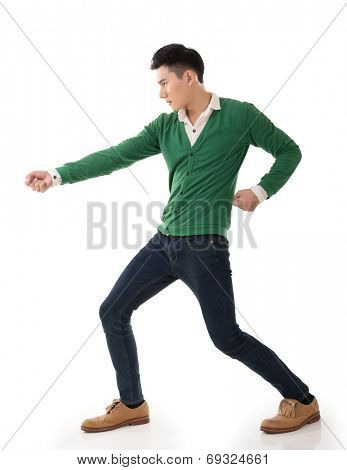 Asian young man posing tug of war, full length portrait isolated on white.