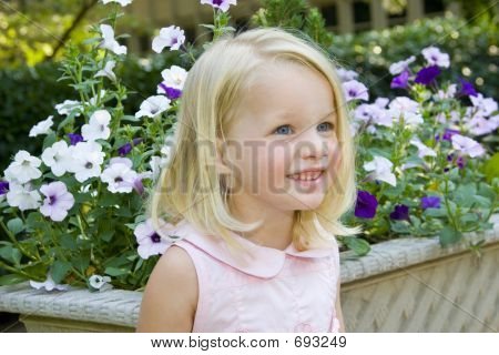 Little Girl In Front Of Flowers