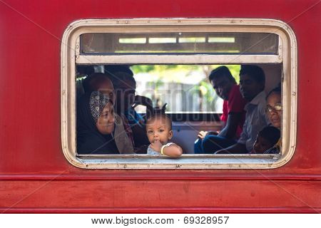 HIKKADUWA, SRI LANKA - MARCH 12, 2014: Local people in train looking through window. Trains are very cheap and poorly maintained but it's the best option to witness a bit of everyday local life.