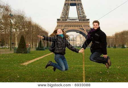 Happy Couple In Paris Jumping Near The Eiffel Tower