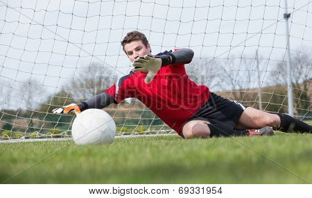 Goalkeeper in red saving a goal during a game on a clear day