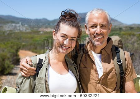 Hiking couple smiling at camera on mountain trail on a sunny day
