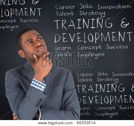 Young businessman thinking against blackboard with business buzzwords