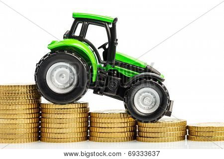 farmers in agriculture have to reckon with rising costs. higher preies in fodder, fertilizer and plants. tractor with coins