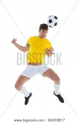 Football player in yellow jersey jumping to ball on white background