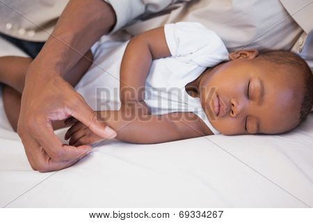 Happy father napping with baby son on couch at home in the living room
