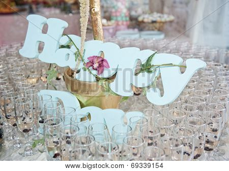 Wedding decor, wine glasses and champagne flutes on table. Glasses of champagne and Happy decoration