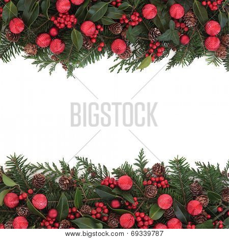 Christmas background  border with red bauble decoration with holly and winter greenery over white.