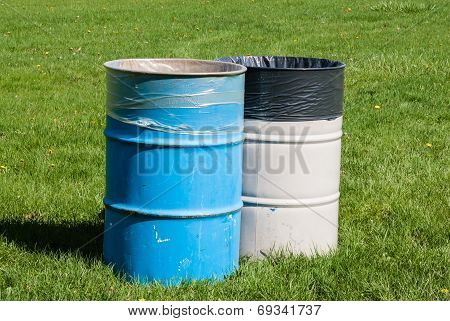 Two Garbage Bins On Green Grass.