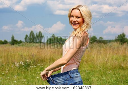 Beautiful young blonde woman standing in a field in wide trousers