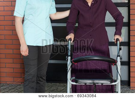 Nurse And Elderly Woman In A Walker Outside