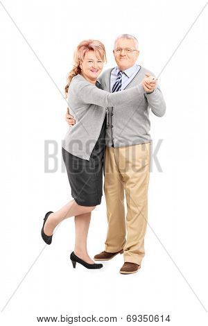 Full length portrait of a mature couple dancing tango isolated on white background