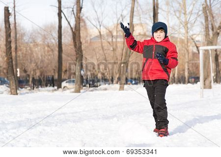 boy in winter park throwing a snowball