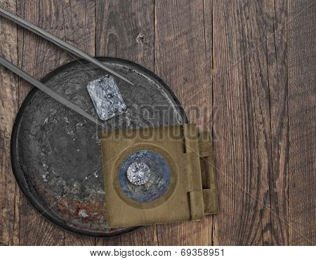 two diamonds in a vintage tin, tweezers and loupe on a wooden bench, space for your text