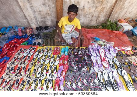 HIKKADUWA, SRI LANKA - FEBRUARY 23, 2014: Young local market vendor selling sandals. The Sunday market is great way to see local life come alive along with fresh produce and local delicacy