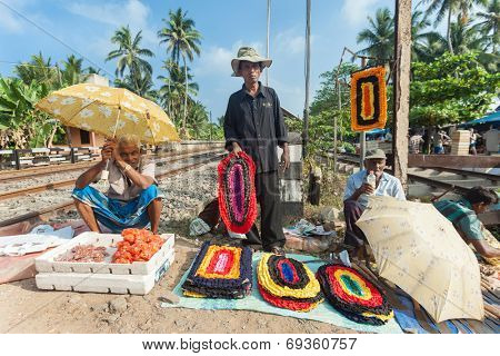 HIKKADUWA, SRI LANKA - FEBRUARY 23, 2014: Local street vendors selling mats by the railroad. The Sunday market is a fantastic way to see Hikkaduwa's local life come alive.