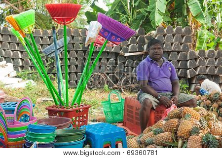 HIKKADUWA, SRI LANKA - FEBRUARY 23, 2014: Local street vendor selling plastic products and pineapples. The Sunday market is great way to see Hikkaduwa's local life come alive along with local delicacy
