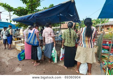 HIKKADUWA, SRI LANKA - FEBRUARY 23, 2014: Local women waiting in line for fresh fish. The Sunday market is a fantastic way to see local life come alive along with fresh produce and local delicacy.