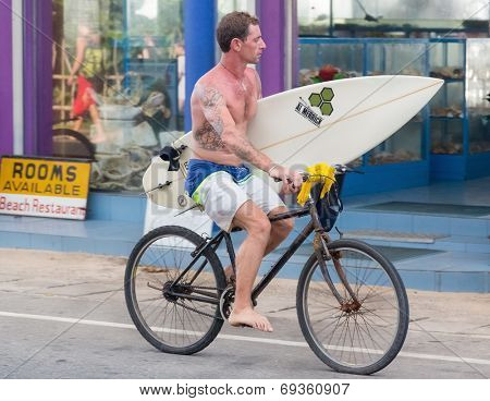 HIKKADUWA, SRI LANKA - FEBRUARY 20, 2014: Tourist  riding a bike while holding surf board. Hikkaduwa is well-known international destination for board-surfing.