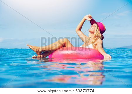 Sexy young woman in bikini relaxing floating in the ocean