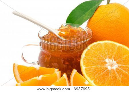 Oranges whole and sliced with jam in a transparent recipient, isolated on a white background