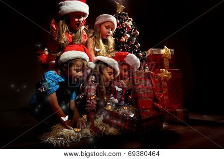 Group of children in Christmas hats open gift with butterflies