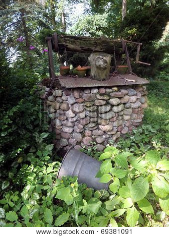 Very Old Well Built Of Stones Overgrown With Weeds,