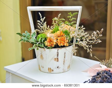 Flower arrangement in white vintage pot. Wedding decoration with yellow flowers. Yellow gerberas