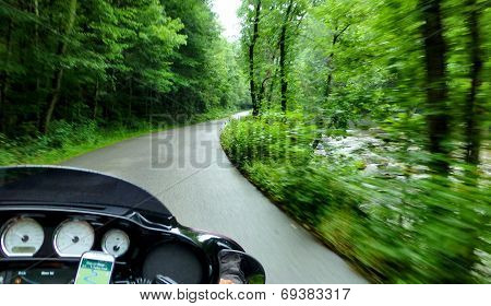 Motorcycle Riding Through The Forest In The Rain