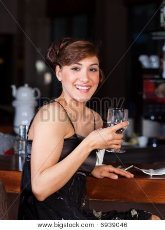 Beautiful Young Woman Drinking Water At Bar