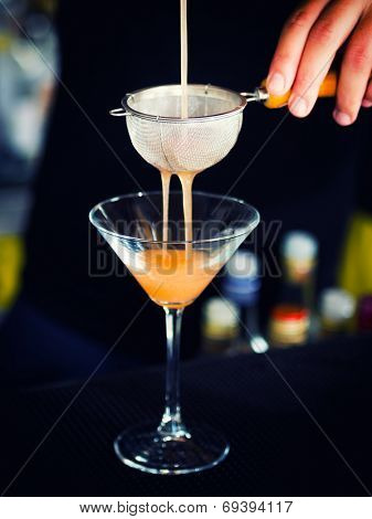 Bartender pouring the cocktail into Martini glass