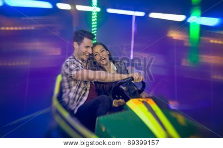 Happy couple having fun laughing and ride bumper car- shoot with lens baby
