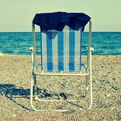 stock photo of naturist  - a deckchair and a man swimsuit on the beach - JPG