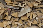 stock photo of firewood  - Some firewood and an axe for making new firewood - JPG