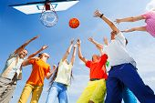 picture of bottom  - Children playing basketball together with a ball up in sky - JPG