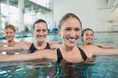 pic of day care center  - Smiling female fitness class doing aqua aerobics in swimming pool at the leisure centre - JPG