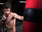 foto of punch  - Young caucasian Boxer training with a punching bag in his home gym - JPG