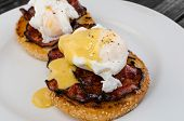 stock photo of benediction  - Benedict eggs with crispy bacon and hollandaise sauce on toasted Maffin on clean plate - JPG