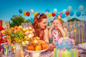 foto of fussy  - Young mother comforts crying baby girl in birthday hat - JPG