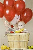 picture of sock-monkey  - An infant boy sitting in a wooden basket with balloons and a sock monkey - JPG