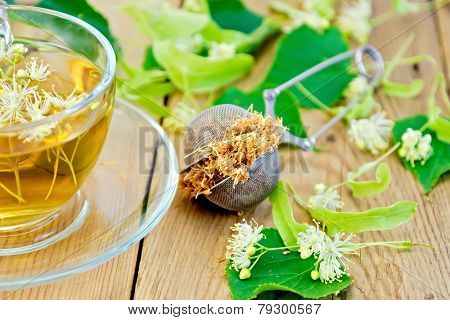 Herbal tea of linden flowers in strainer with cup