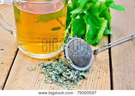 Herbal tea with mint in mug with strainer on board
