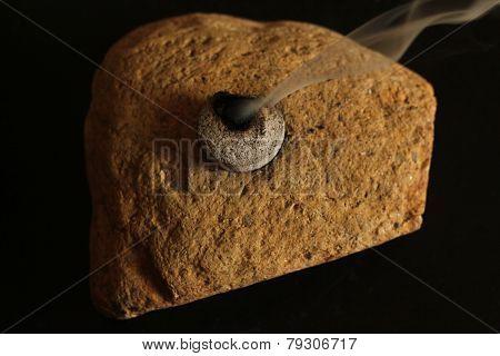 Charcoal burning on rock