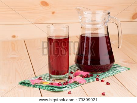 Glass and carafe of pomegranate juice.