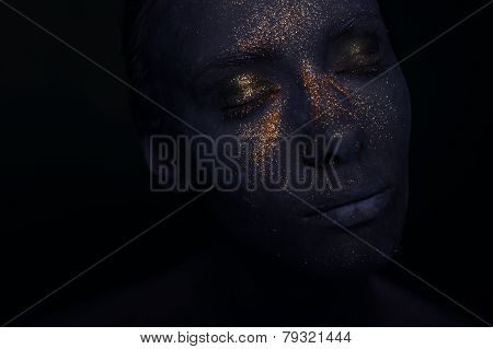 portrait of woman in blue paint and golden dust