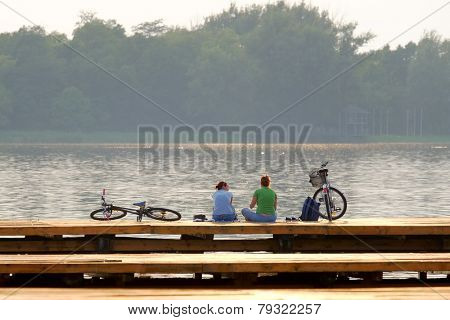 SUBOTICA, PALIC LAKE, SERBIA: two women with bikes are relaxing at the sunset on a wooden pier of Palic Lake near Subotica, Serbia. Shot in 2014