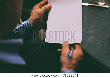 Man Reading Contract At The Table