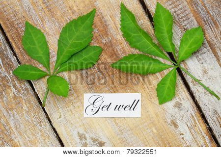 Get well card with two green leaves on rustic wooden surface