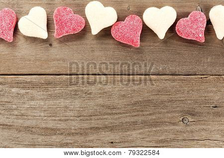 Valentines Day candy border on wood background