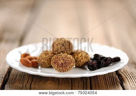 Homemade Almond Candies On White Plate With Almond And Raisins